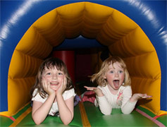An image of two children playing in an inflatable